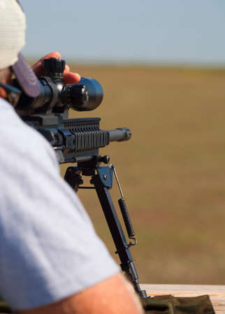 Shooter behind an AR-15 changing elevation for a long shot