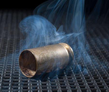 semi automatic: Semi automatic handgun brass on a black grate with smoke