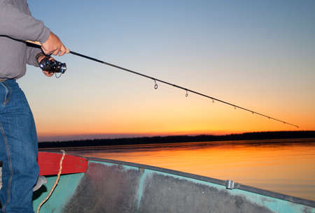 spinning reel: Man working a spinning reel as the sun is going away in Saskatchewan Canada Stock Photo
