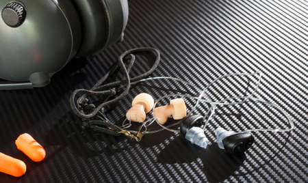 earpiece: Different styles of hearing protection on a graphite background Stock Photo