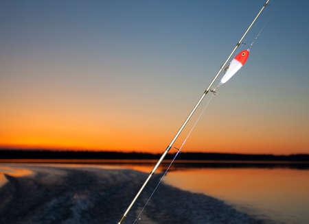 saskatchewan: Twilight fishing rod and lure on a lake in Saskatchewan Canada