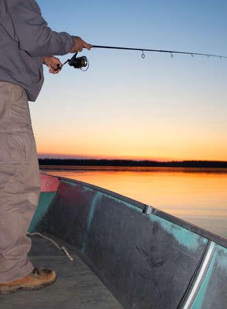 saskatchewan: Fisherman who is fishing from a boat at sunrise in Saskatchewan Canada Stock Photo