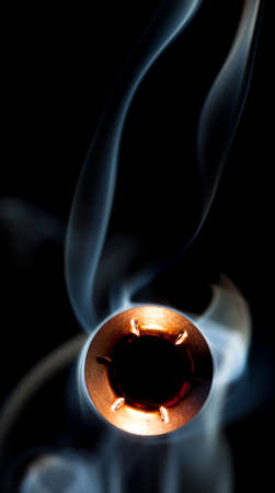Hollow point bullet and smoke bearing down on the viewer