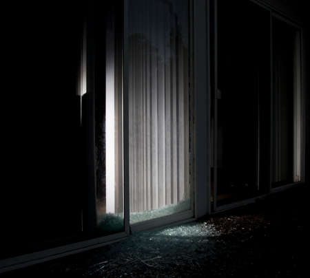 nightime: House with a shattered sliding glass door and flashlight on inside