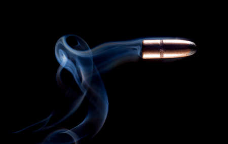 copper coated: Copper coated lead bullet with smoke on a black background Stock Photo