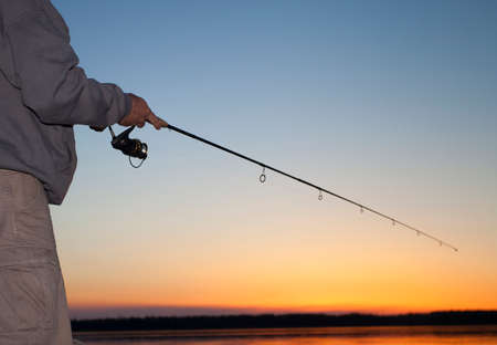 spinning reel: Spinning reel in the hands of an angler at sunset at Saskatchewan Canada