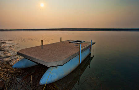 pontoon: Lake in Canada at sunrise with a pontoon boat on shore