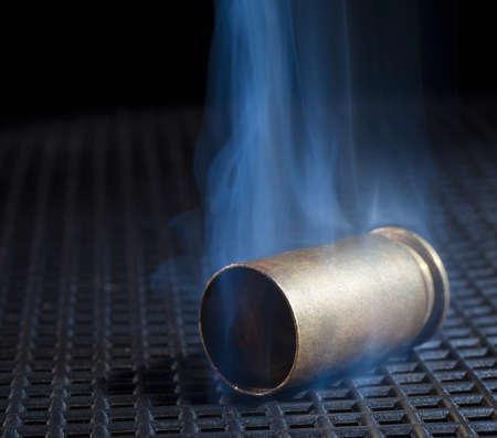 Handgun brass with smoke on a black grate 写真素材