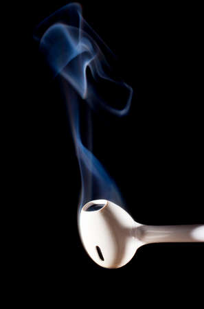 earbuds: White earphone that is smoking on a black background Stock Photo