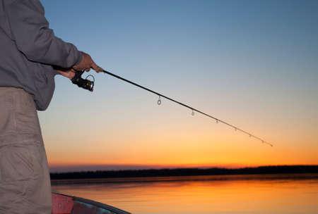 saskatchewan: Man working a spinning real at sunset in Saskatchewan Canada Stock Photo