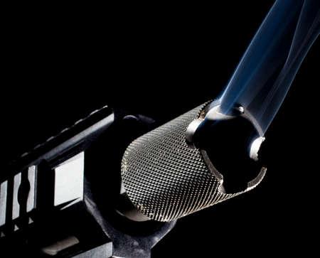 semi automatic: Smoke coming from the barrel of a semi automatic firearm Stock Photo