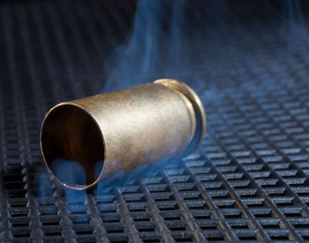 the casing: Empty brass casing from a handgun with smoke rising
