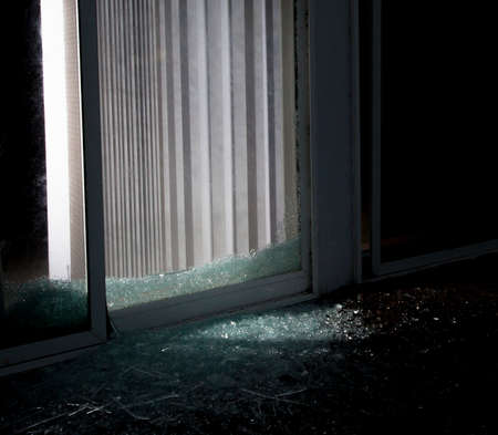 nightime: Light coming from inside a shattered sliding glass door that could be the burglar