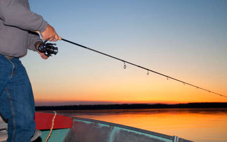 spinning reel: Spinning reel being worked at last light on a lake in Saskatchewan Canada