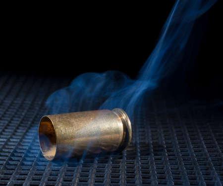 grate: Empty handgun brass with smoke on a black grate