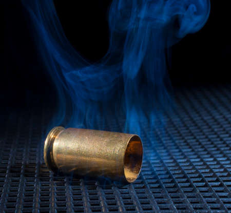 semi automatic: Empty shell from a semi automatic handgun that is smoking
