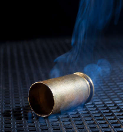 Handgun shell after being fired with smoke rising 写真素材