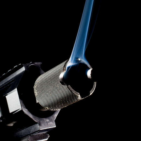 Barrel on a semi automatic gun with a black background and smoke