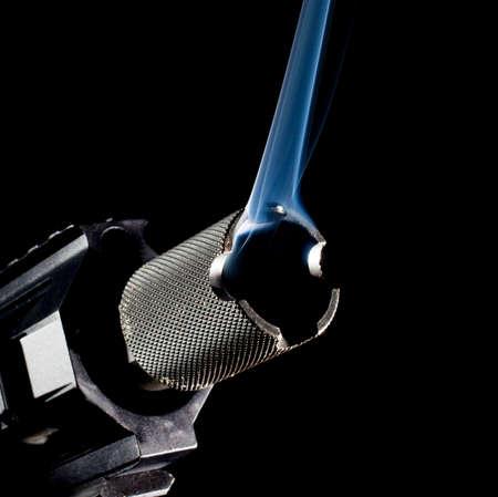 semi automatic: Barrel on a semi automatic gun with a black background and smoke