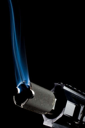 Short modern sporting rifle on black with smoke coming from the barrel Banco de Imagens