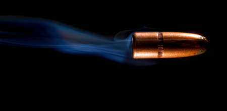 projectile: Lead bullet with a copper plate on black with smoke behind Stock Photo