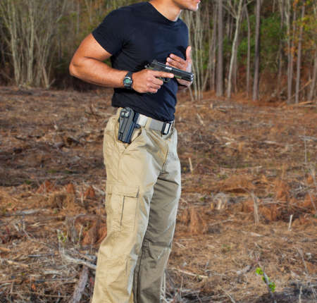 holster: Man drawing a semi automatic handgun from its holster