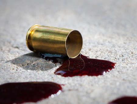 Single piece of handgun brasa on concrete with blood around