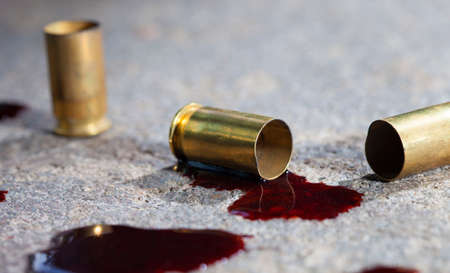 casings: Casings that have been shot from a handgun with blood on concrete