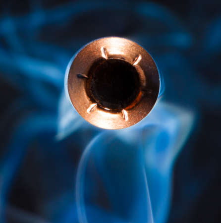 bullet camera: Hollow point bullet with a copper jacket and smoke coming at the camera Stock Photo