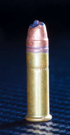 gash: Lead bullet with a gash still on a rimfire cartridge