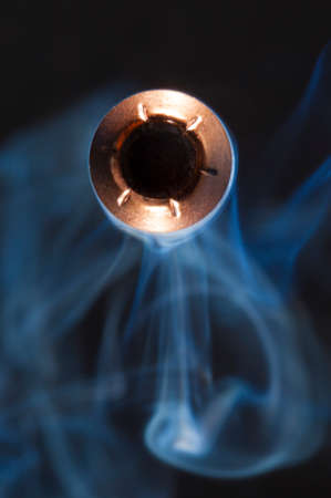 bullet camera: Bullet with a hollow point looking at the camera and smoke behind Stock Photo