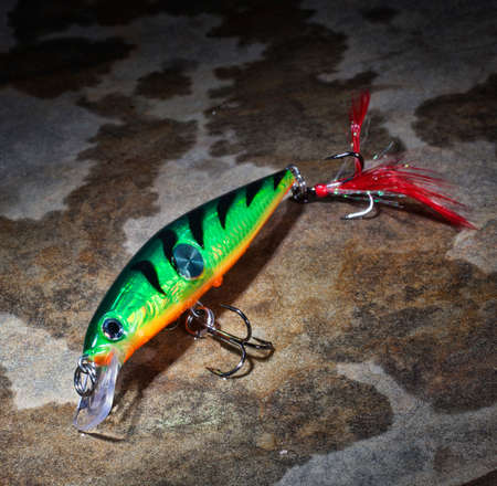 fishing lure: Green fishing lure with orange underneath on a wet rock