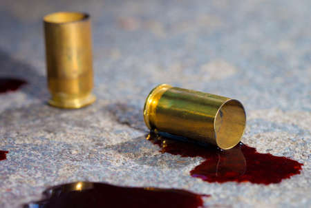 two pieces: Two pieces of handgun brass on concrete with blood