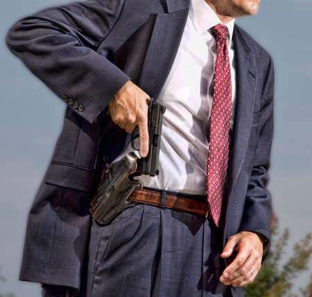 Persoon met een verborgen carry vergunning uitgangspunt om zijn pistool te trekken Stockfoto