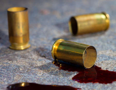 casings: Handgun casings on concrete with blood around the brass