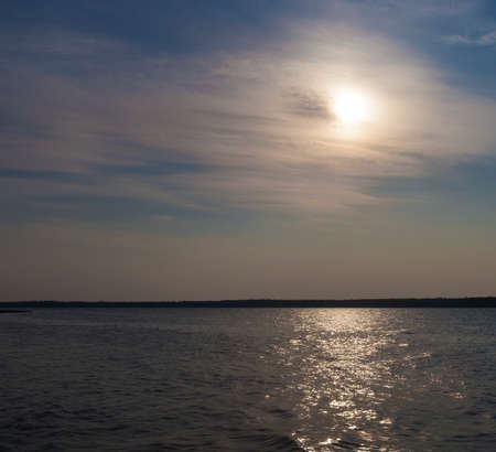 obscuring: Thin clouds obscuring the sun temporarily over a Saksatchewan Canada lake Stock Photo
