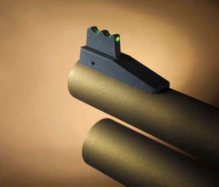 Bright fiber optic sight on the front of a gold colored shotgun