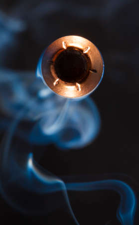 Copper jacketed hollow point direct at the camera with smoke behind Stock Photo