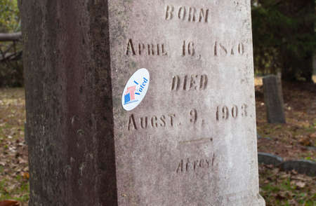 voted: Grave marker that has a sticker that says I voted