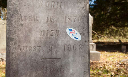voted: Tombstone that has a sticker on it that says I voted