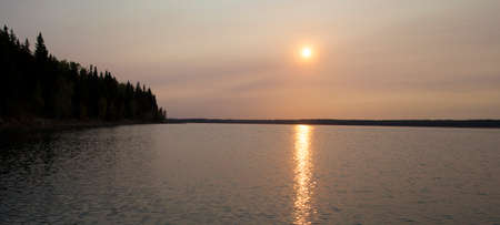 adds: Smoke from a fire in nearby Albert adds color over Dore Lake Saskatchewan at dawn