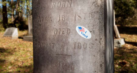 i voted: I voted sticker on a tombstone in a graveyard