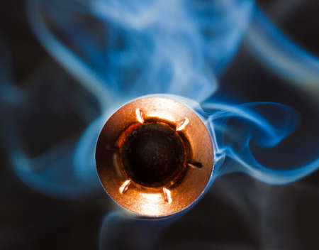Bullet from a pistol that is a hollow point with smoke behind Stok Fotoğraf