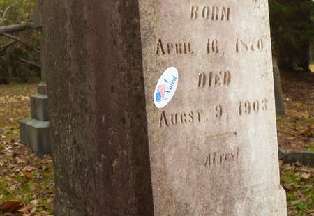 voted: Tombstone that is wearing an I voted sticker Stock Photo