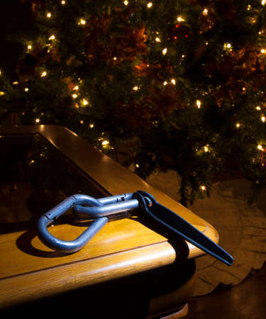 Pair of carabiners and a piton near a lit Christmas tree Stock Photo