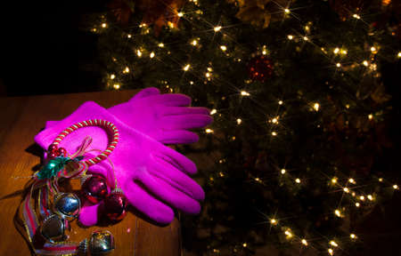 Pink gloves on a table with a Christmas tree with lights behind Stock Photo