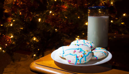 lighted: Cookies with white frosting and milk next to the Christmas tree
