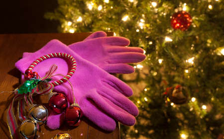 Bright pink gloves on a table with a lit Christmas tree behind Stock Photo