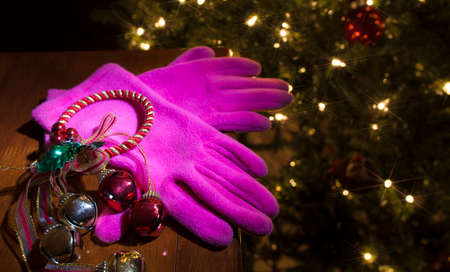 New pink gloves that have been gifted with a Christmas tree in the background Stock Photo