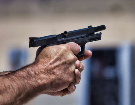Handgun that has just been fired and an empty case is flying